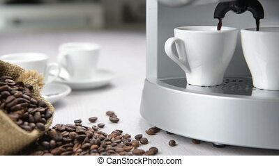 coffee machine in operation fills two white cup with coffee...