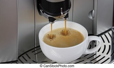 Coffee machine pouring espresso in cup macro image.