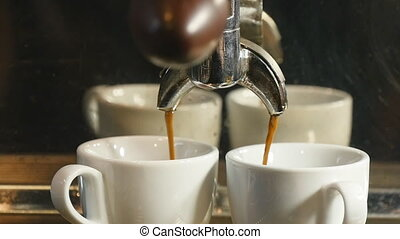 Coffee machine pouring espresso into the cup in slowmotion