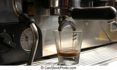 Coffee machine pours espresso. Shot glass close up.