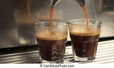 Coffee maker fills glasses. Fresh coffee close up.