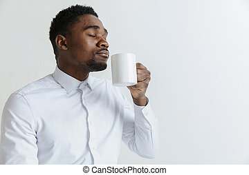 Coffee makes his day. Young handsome African man drinking coffee and looking away while sitting at his working place
