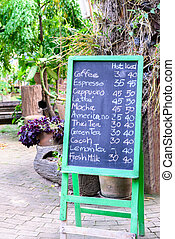 Coffee menu hand written in English with chalk on green frame blackboard.