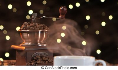Coffee mill with beans. Closeup smoke with a white cup -...