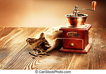 Coffee mill with burlap sack full of roasted coffee beans over wooden vintage table