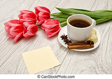 Coffee mug with spices, clean note, pink tulips on a wooden background, spring breakfast