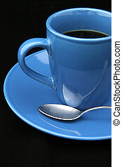 Coffee on Black - A bright blue cup of coffee with a spoon,...