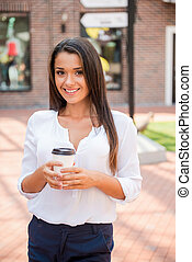 Coffee on the Go. Beautiful young woman holding coffee cup and smiling while standing outdoors