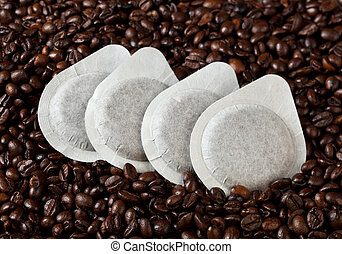 Coffee pods on coffee beans background