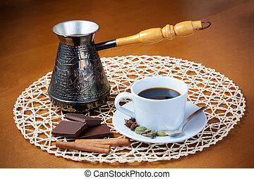 Coffee pot, cup of coffee with spices and pieces of chocolate