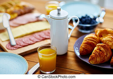 coffee pot, juice and food on table at breakfast