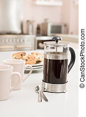 Coffee pot on kitchen counter with scones