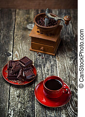 Coffee red cup, pieces of chocolate on wooden table background. Tinted. Selective focus.