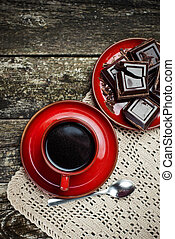Coffee red cup, pieces of chocolate on wooden table background. Tinted. Top view.