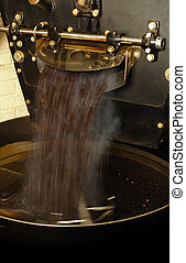 A large coffee roaster, as the roasted beans are extracted and slowly stirred in the cooling cylinder.
