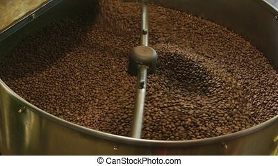 Coffee roaster in motion. Lots of coffee beans. How to...