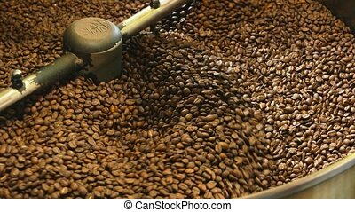 Coffee roasting machine close up. Lots of dark coffee beans....