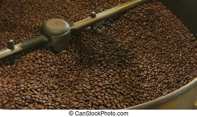 Coffee roasting machine. Dark coffee beans.
