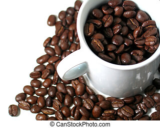 A mug filled with coffee beans, surrounded by more coffee beans. Focus on beans in the white mug.