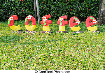 coffee shop sign on green grass