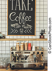 coffee shop - coffee machine, glassware and paper cups in...