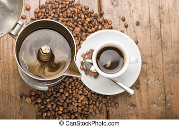 coffeepot and cup of coffee with coffee beans on wooden...