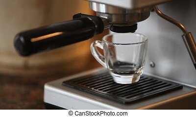 coffee - Coffee maker pouring hot espresso coffee in glass...