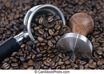 Roasted coffee surrounds a tamper and filter...it's coffee time...