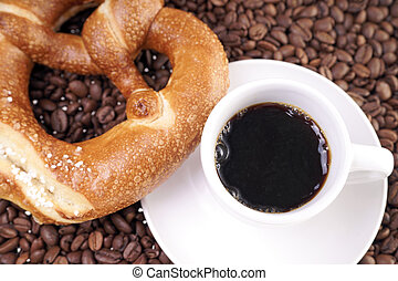 Cup of coffee with pretzel and coffee beans