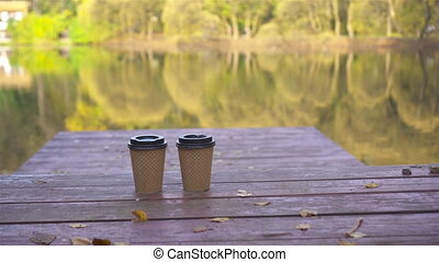 Two glasses of hot takeaway coffe on a wooden pier at the lake on an autumn day