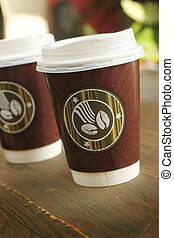 Coffee to go - Two cup of coffee to go on a wooden table