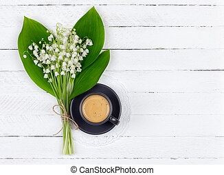 coffee with cream in a black Cup on a saucer and a bouquet of Lily of the valley flowers with green leaves on a white wooden background with copy space, top view flat lay