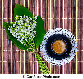 coffee with cream in a black Cup on a saucer and a bouquet of Lily of the valley flowers with green leaves on a brown wooden background, top view flat lay