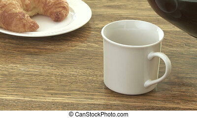 Coffee with croissant - Pouring coffee with croissant on the...