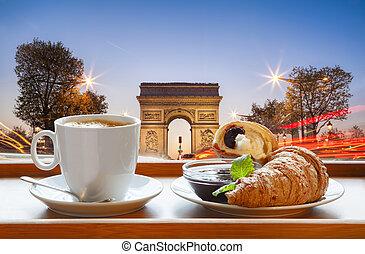Coffee with croissants against Arc de Triomphe in Paris, France