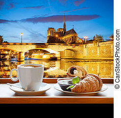 Coffee with croissants against cathedral Notre Dame in...