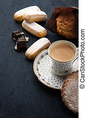 Coffee with different sweets on the dark table vertical
