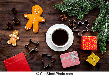 Coffee with gingebread cookies and gifts in christmas evening. Dark wooden background top view
