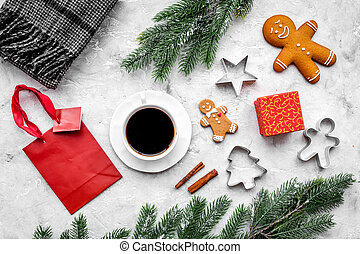 Coffee with gingebread cookies and gifts in christmas evening. Grey stone background top view