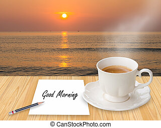 """Coffee with """"Good morning"""" on paper note in the beach"""