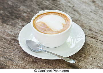 coffee with pattern in a white cup on wooden background