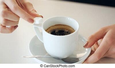 woman adding sugar to coffee