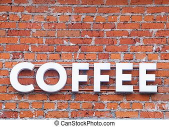 Coffee word in bulk letters on a brick wall