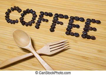 Coffee word with wooden spoon and fork on table
