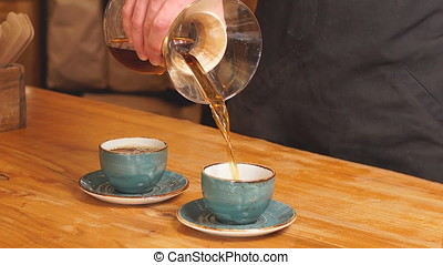 Coffeemaker is pouring beverage into the cups.