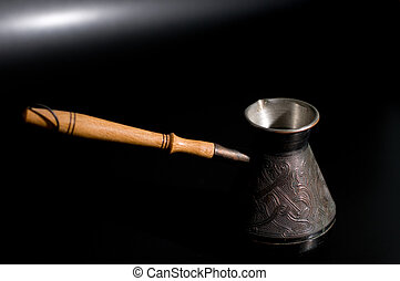 traditional Turkish copper coffee pot against black background