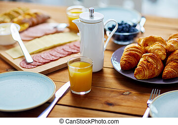 coffeepot and glass of juice on table at breakfast