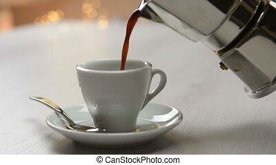 coffeepot pouring black coffee into cup on table.