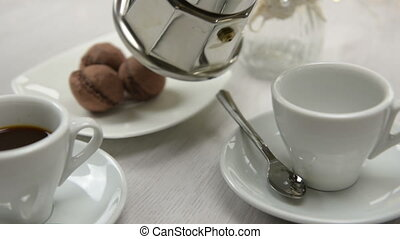 coffeepot pouring black coffee into cup on table. Shooting...
