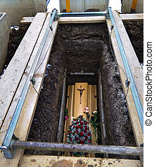 A coffin shortly after the funeral in an open grave